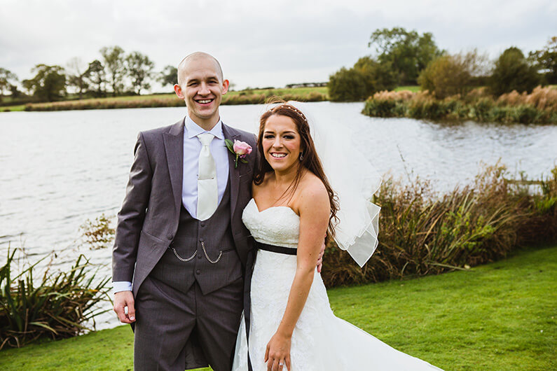 Claire and Sam beside the beautiful lake at Sandhole Oak Barn