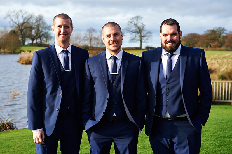 Groom and groomsmen in navy blue suits at Sandhole Oak Barn