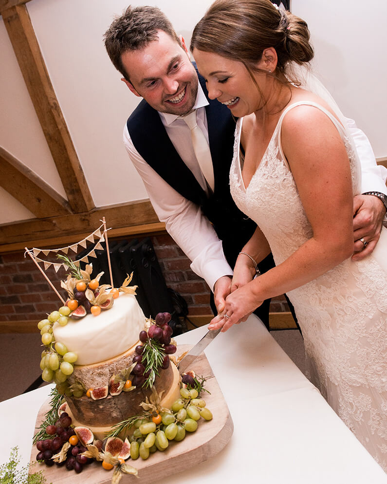 Chloe and Richard cutting their cheese wedding cake