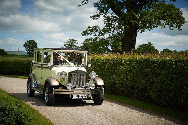 A vintage cream Rolls Royce arriving at Sandhole Oak Barn