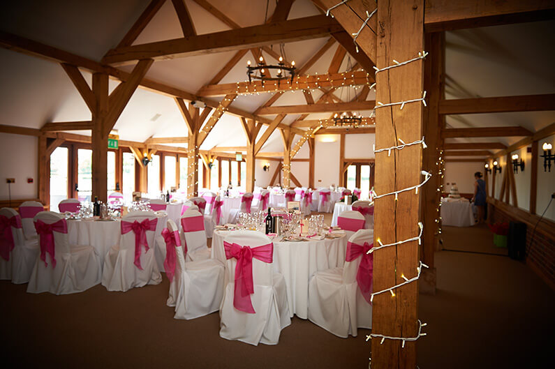 White chair covers with bright pink sashes