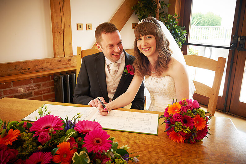 Surrounded by brightly coloured flowers signing the register