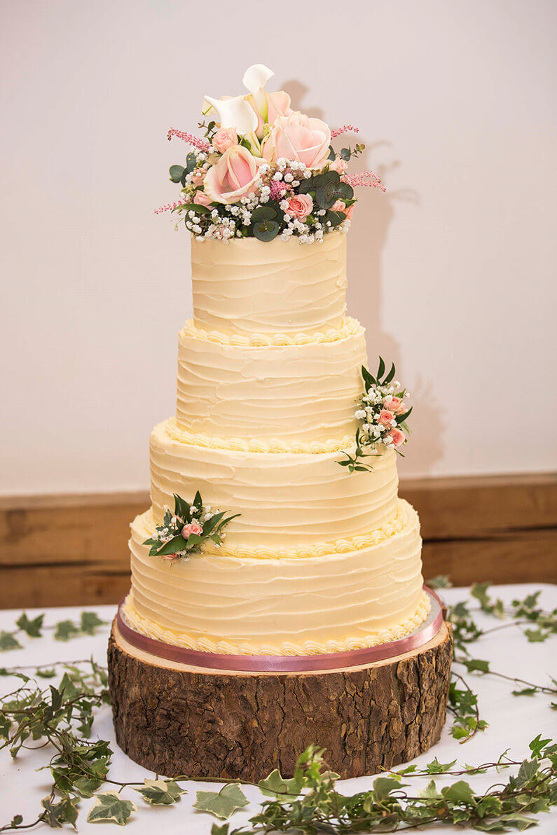 Cream 4 tiered wedding cake with floral decorations