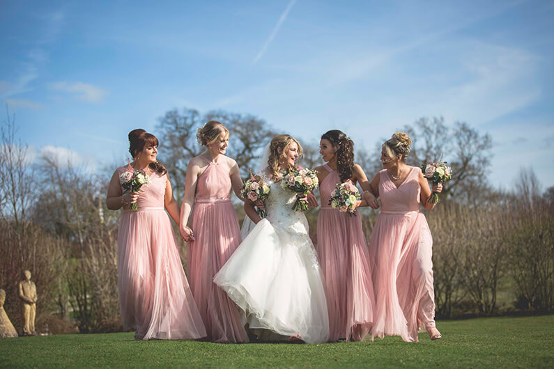 Micaela with her bridesmaids in blush pink dresses