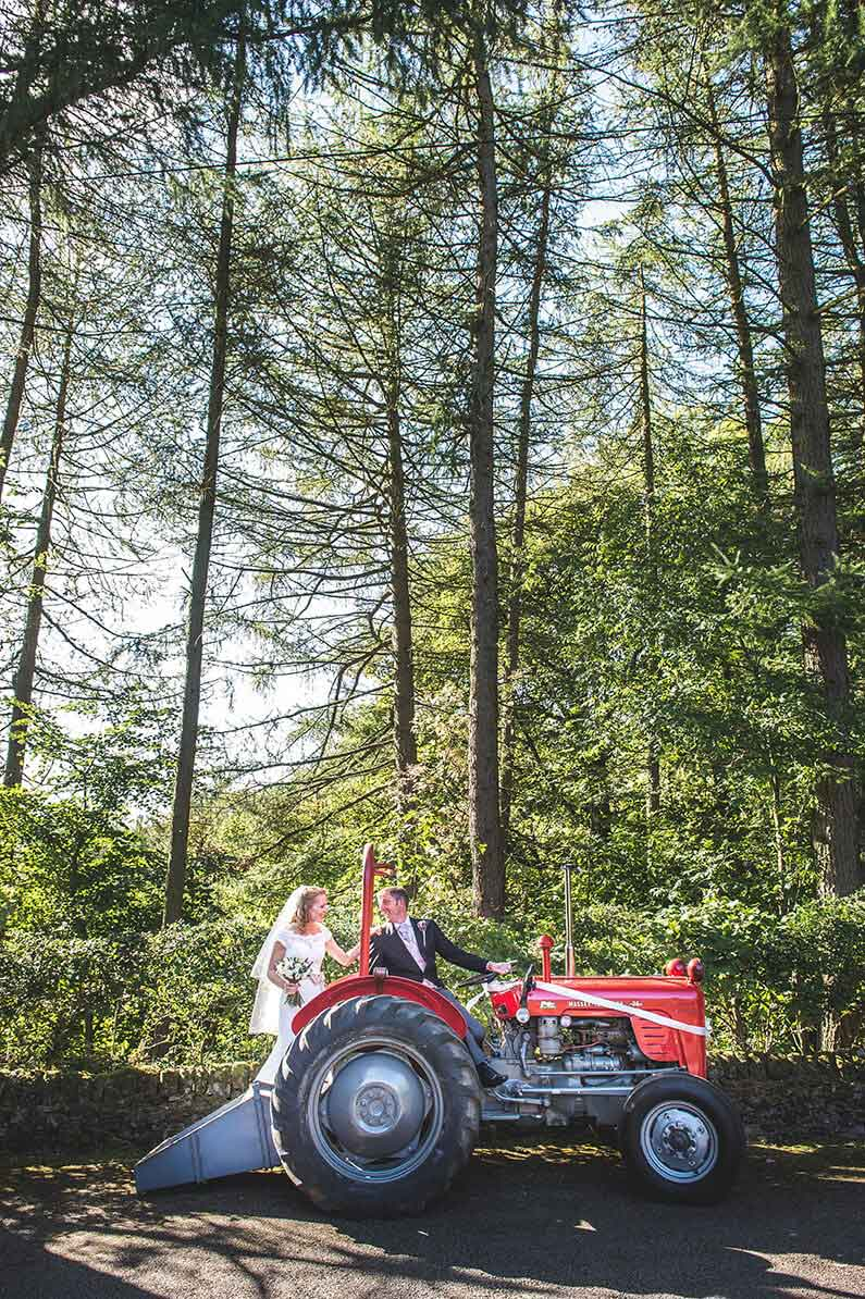 Rachel and Norman with a red tractor at Sandhole Oak Barn