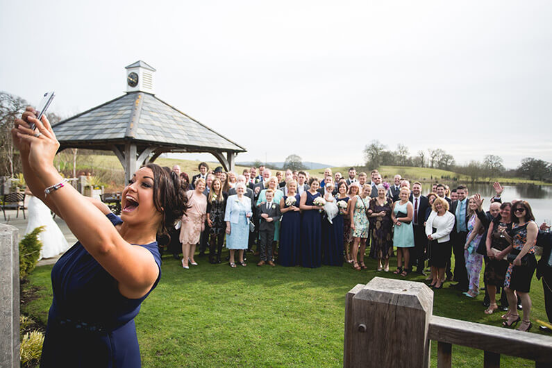Bridesmaid in navy dress taking a group selfie