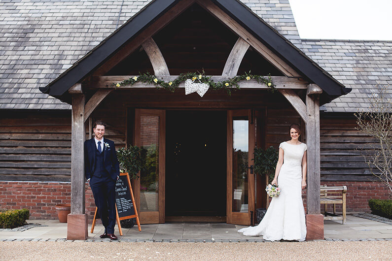 Lauren and Danny posing outside the rustic barn