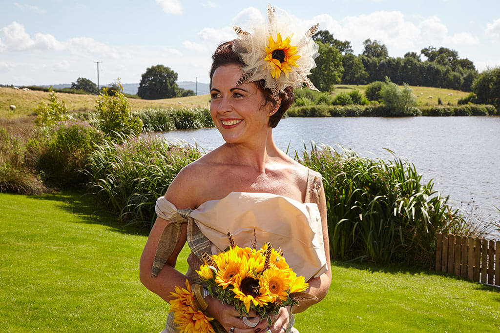 Bride wearing cream dress with sunflower bouquet