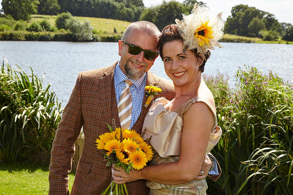 Bride and groom outside lake with yellow sunflowers