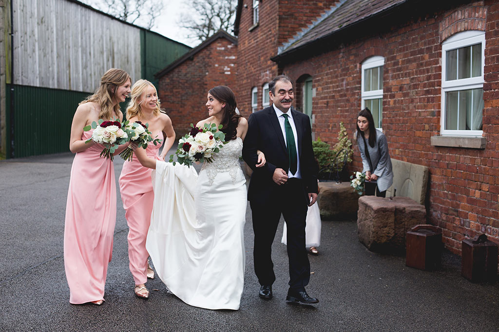Bride and bridesmaids walking to the country house wedding venue