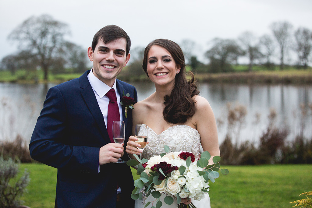 Bride and groom stood infront of the lake at sandhole oak barn