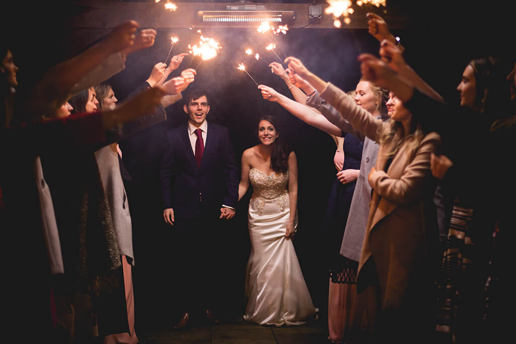 Sparklers held above bride and groom in wedding celebrations