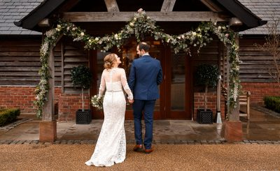 A bride and groom hold hands as they enter the stunning Cheshire wedding barn