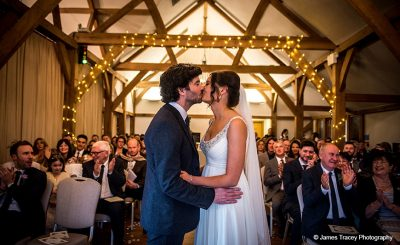 A happy couple kiss after tying the knot at this barn wedding venue
