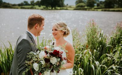 A bride and groom steal a moment by the lake at one of the finest wedding venues in Cheshire