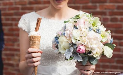 A bride enjoys ice cream at her summer wedding at Sandhole Oak Barn
