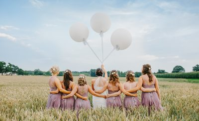 A bride and her bridesmaids stand in a corn field holding balloons – summer wedding ideas