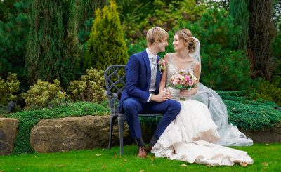 A couple steal a moment in the gardens at Sandhole Oak Barn during their autumn wedding