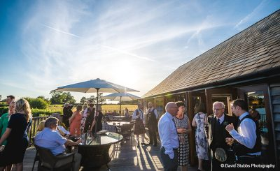Guests enjoy the terrace at Sandhole Oak Barn wedding venue