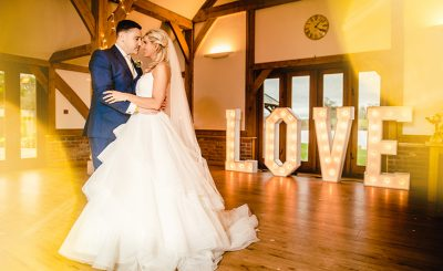 A pair of happy newlyweds take to the dance floor in the rustic wedding barn to enjoy their first dance
