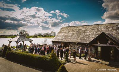 Guests enjoy a drinks reception at Sandhole Oak Barn winter wedding venue