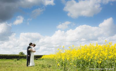 A happy couple kiss amongst the flowers at Sandhole Oak Barn