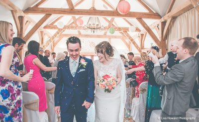 Happy couple leave the ceremonny barn wedding venue