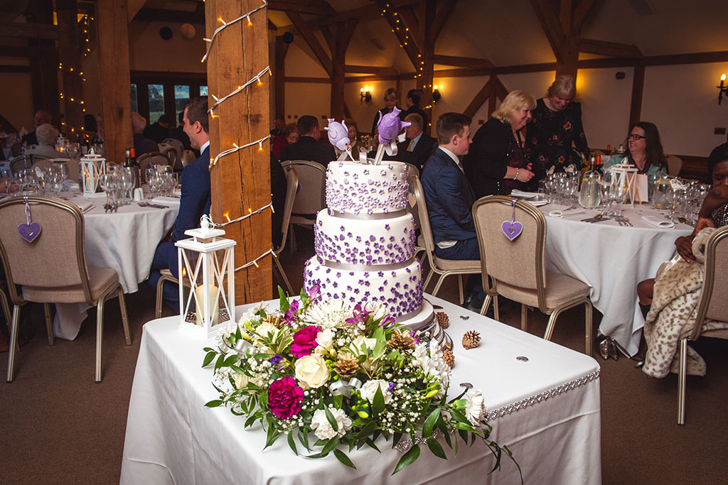 3 tier wedding cake with purple decoration at Kirsty and Richard's wedding at Sandhole Oak Barn