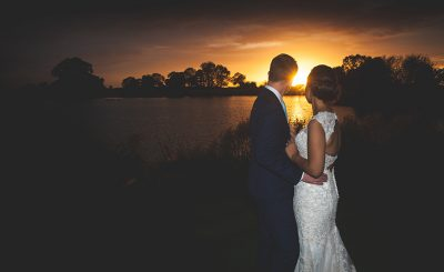 A bride and groom watch as the sun sets on the lake at this stunning wedding venue in Cheshire