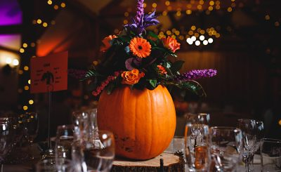 A pumpkin filled with orange and purple flowers makes a fabulous wedding centrepiece at an autumn wedding