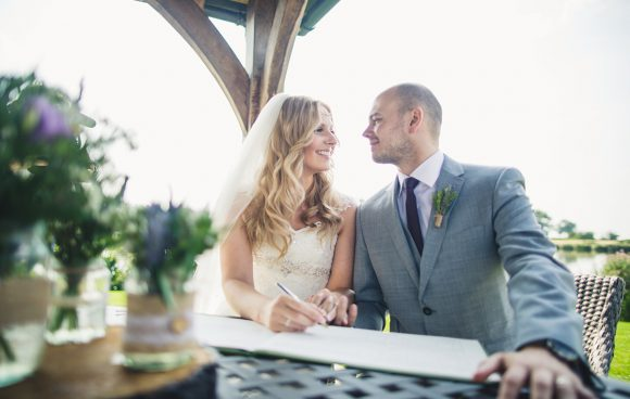 Couple signing register after saying I do at Sandhole Oak Barn wedding venue