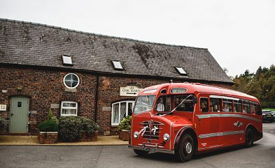 A red vintage wedding bus arrives with guests at one of the finest wedding venues in Cheshire