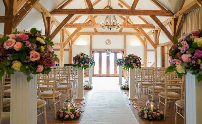 The beautiful barn is set up for a wedding ceremony with wedding flower arrangements lining the wedding aisle