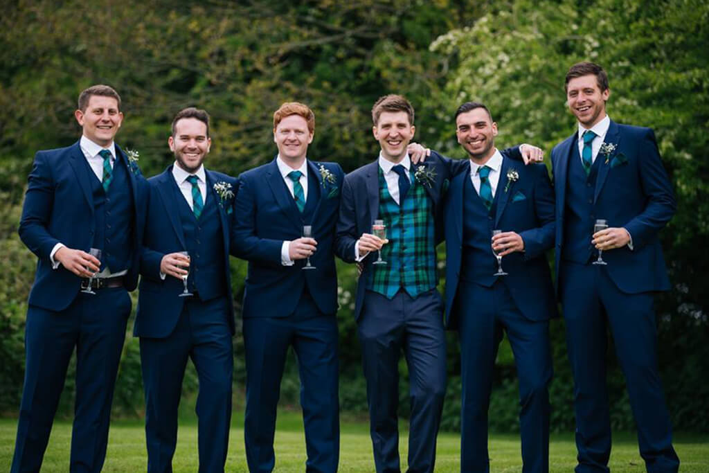 The groom stands with his groomsmen each wearing striking blue suits with tartan waistcoats