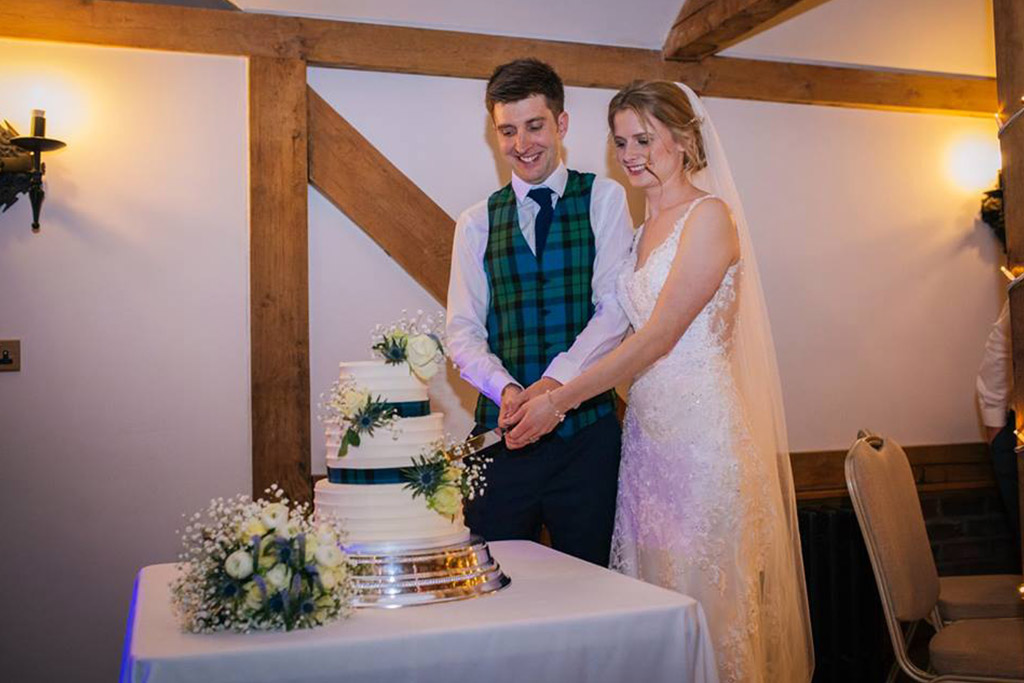 The happy newlyweds cut their three-tiered wedding cake decorated in white roses and a deep blue ribbon