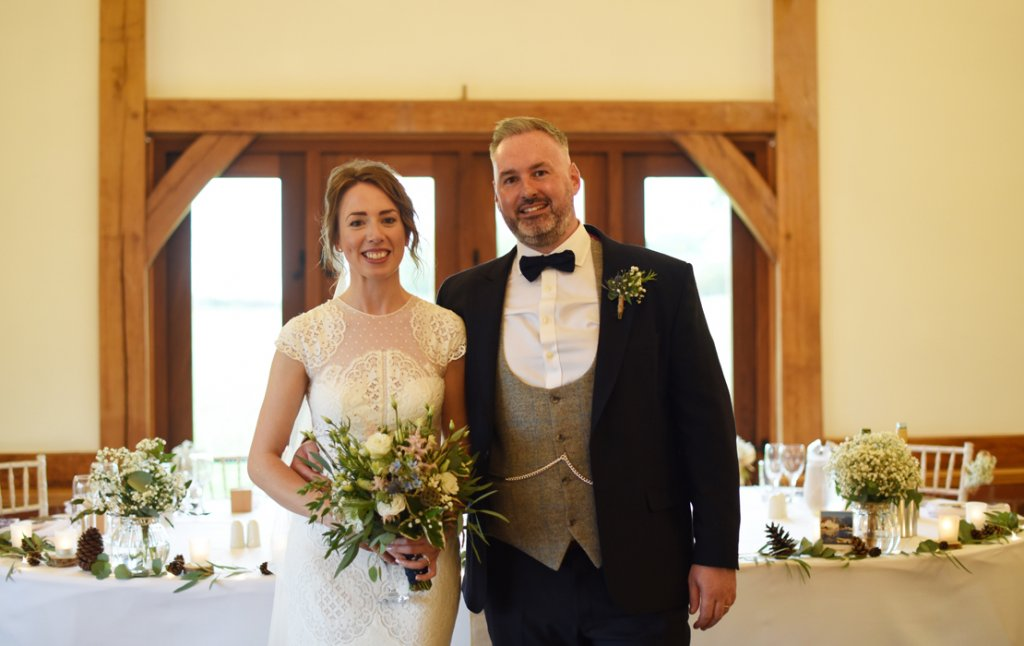 The happy newlyweds pose for a wedding photo at Sandhole Oak Barn in Cheshire