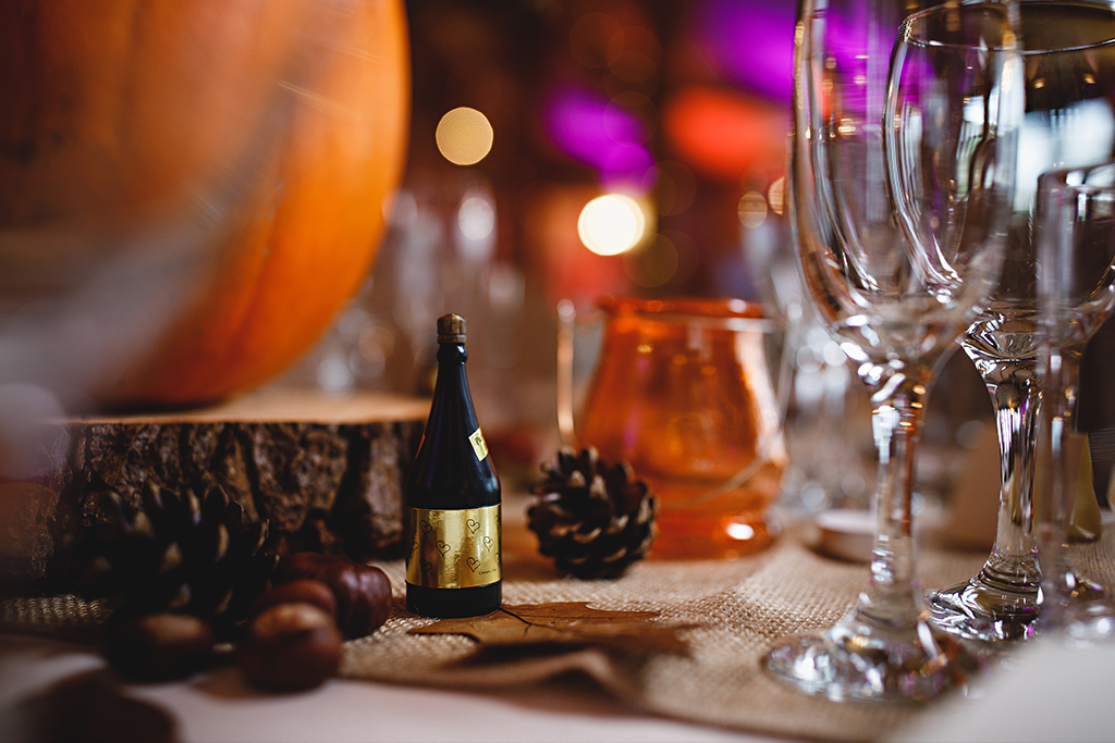 Pumpkins set on wood slices and scattered rustic decorations create the perfect autumn wedding table display