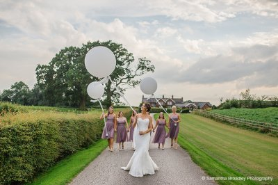 The bride has a photo taken with her bridesmaids holding white wedding balloons at this wedding barn in the North West