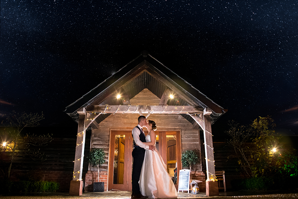 The happy couple pose for a wedding photo on a snowy evening at this wedding venue in Cheshire