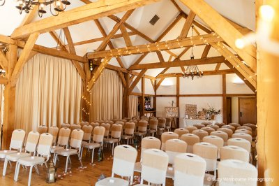 The Oak Barn is set up ready for the wedding ceremony and has been decorated in natural colours at this North West wedding barn