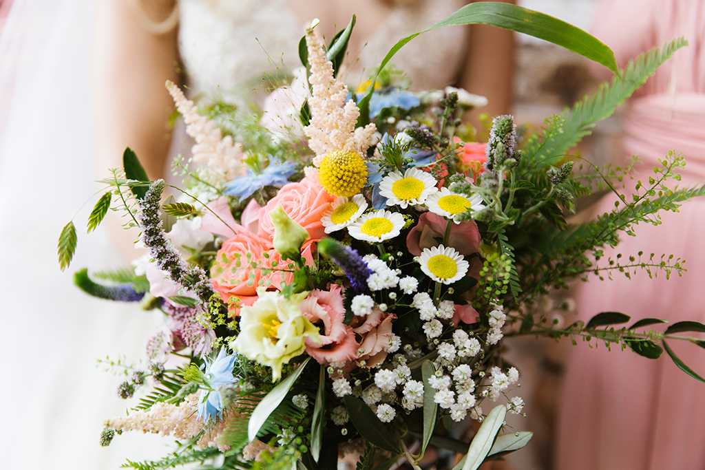 The bride's bouquet was a stunning mix of colourful summer flowers and lush foliage at this summer wedding at Sandhole Oak Barn