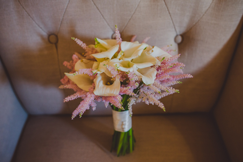 The brides bouquet was made from beautiful white calla lilies and pastel pink astilbe at this barn wedding at Sandhole Oak Barn
