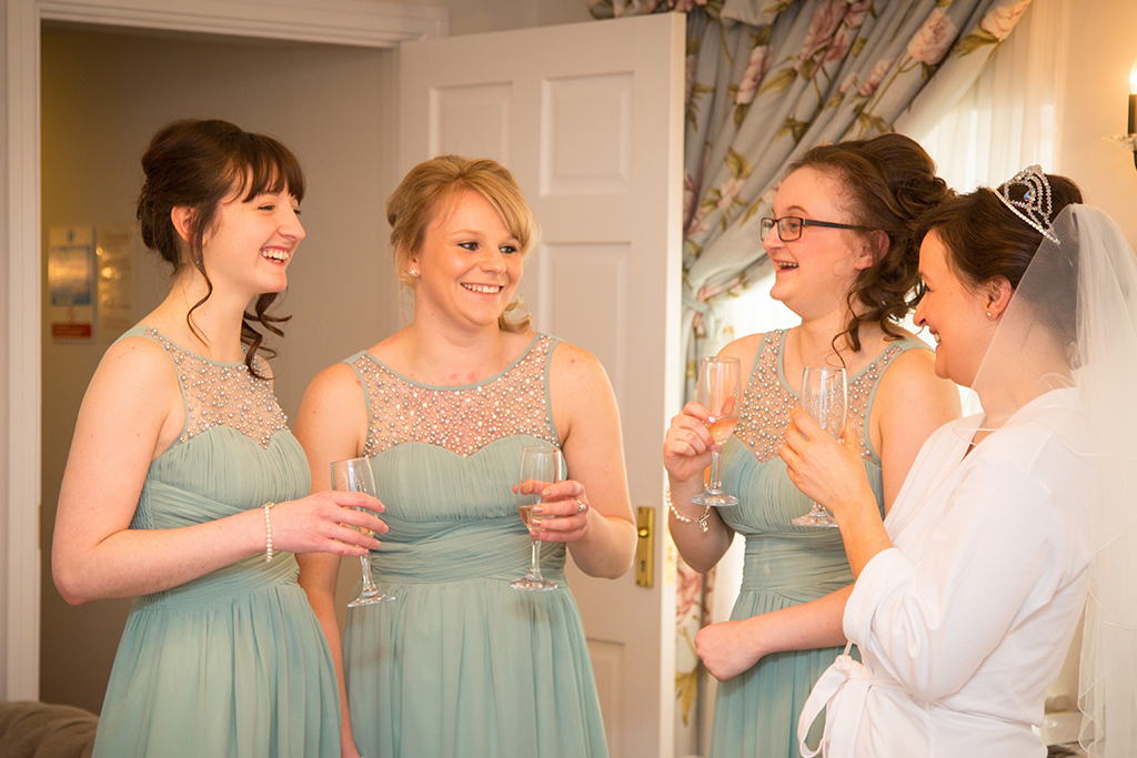 The bride and her bridesmaids in their pastel blue dresses enjoy a toast while the bride prepares to be married