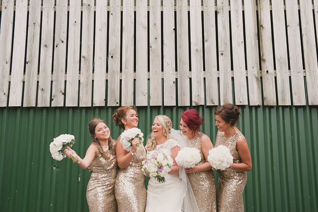 The bride laughs with her bridesmaids who each wore long gold sparkly bridesmaid dresses