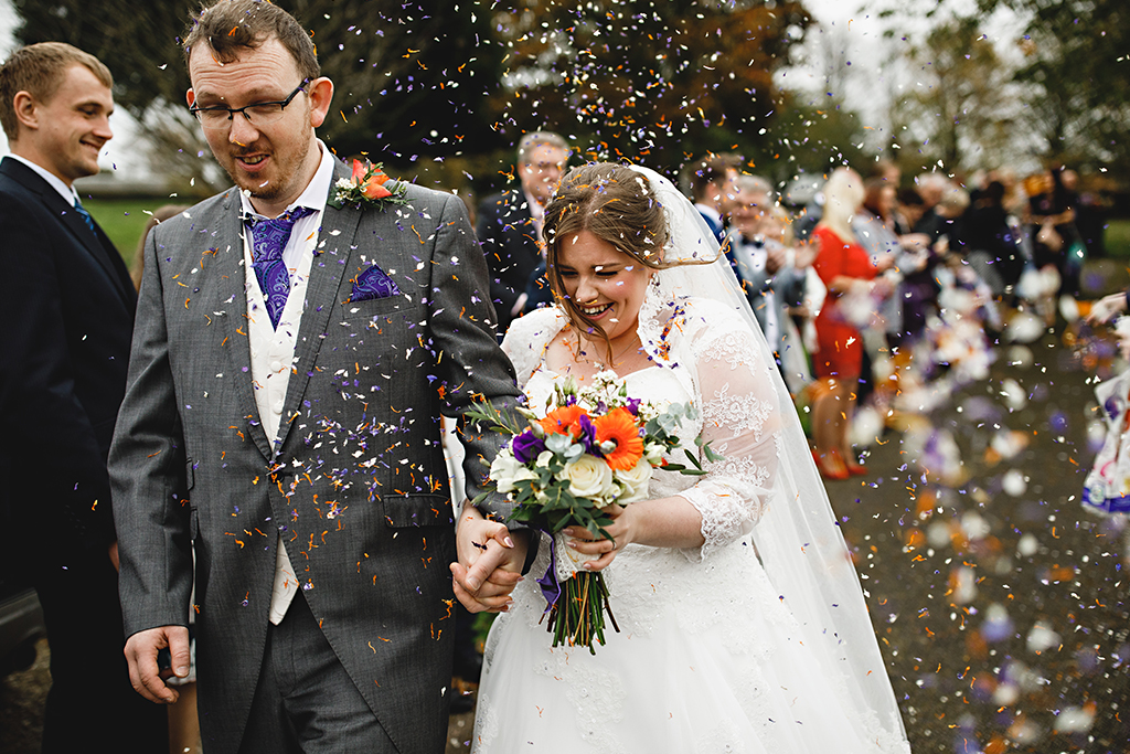 Guests throw colourful natural confetti over the newlyweds at this barn wedding in Cheshire