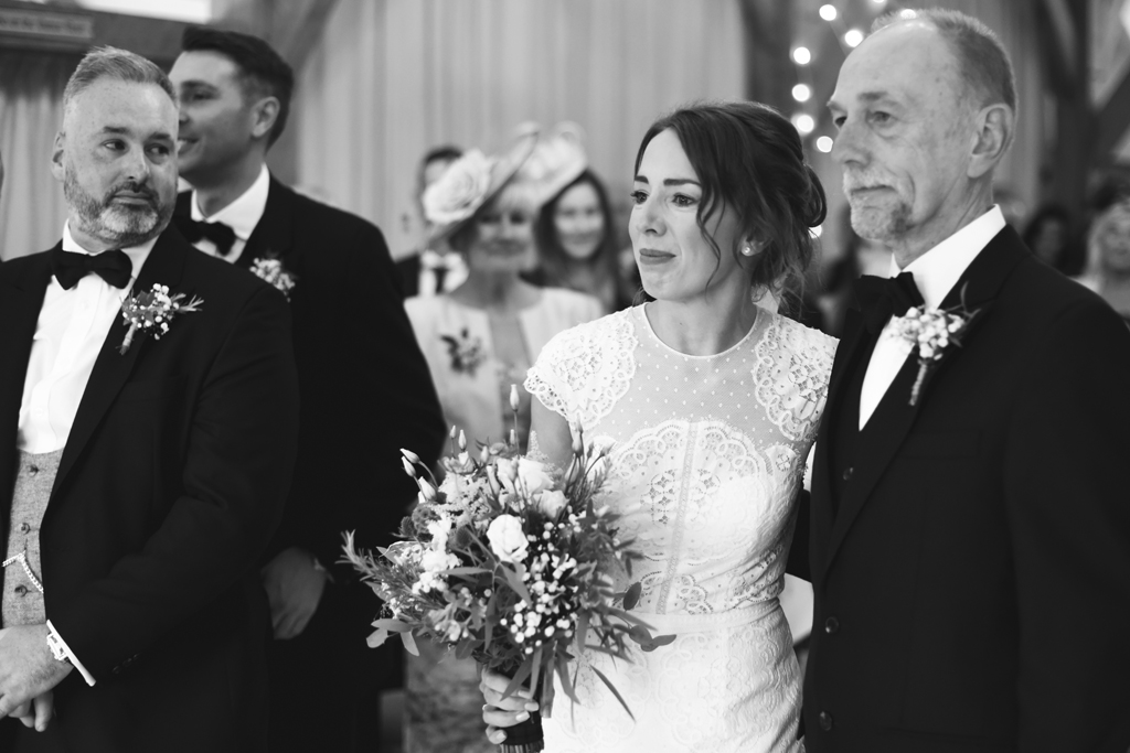 The groom takes a glance at his beautiful wife to be at the wedding ceremony at Sandhole Oak Barn in Cheshire