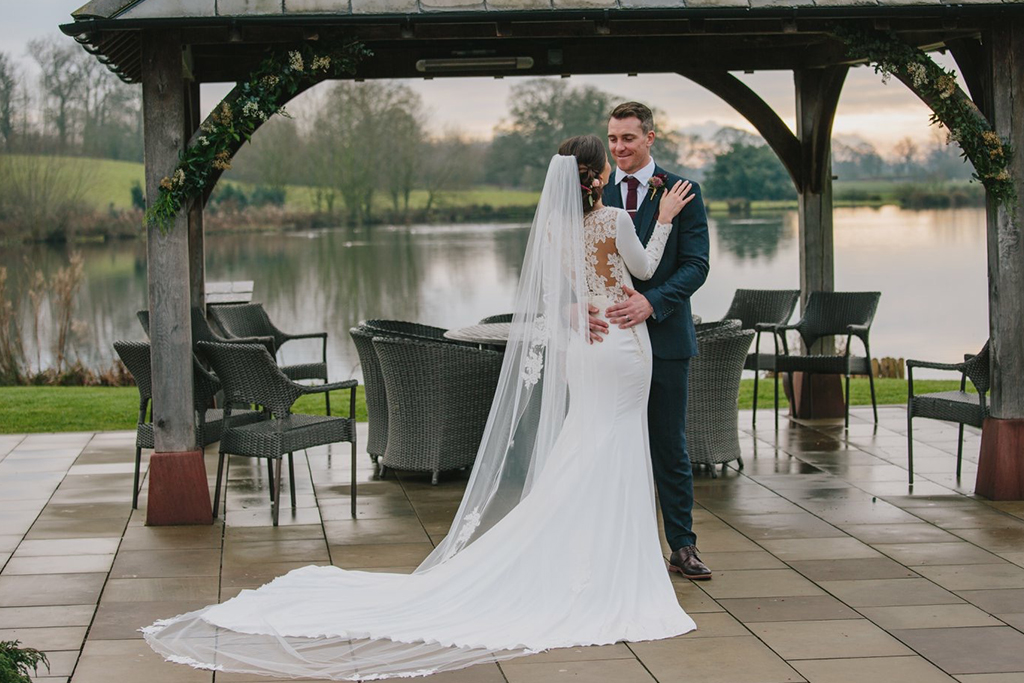 The happy newlyweds pose for a photo by the Clock tower at this lakeside wedding venue near Manchester
