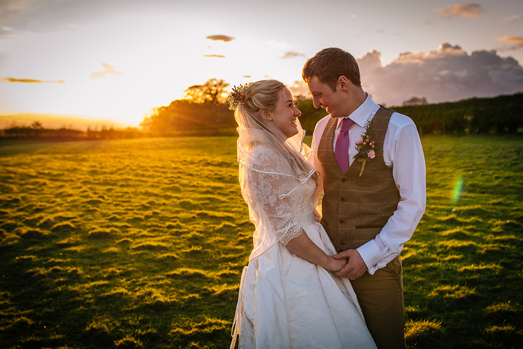 The happy couple have their photo taken in the stunning sunset at this rural wedding venue in Cheshire