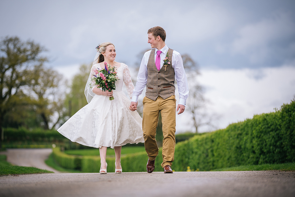 The happy newly weds take a stroll down the drive at Sandhole Oak Barn at their rustic barn wedding