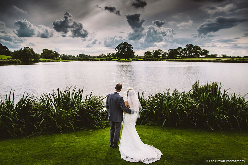 A bride and groom admire the views across the lake at Sandhole Oak Barn wedding venue in Cheshire